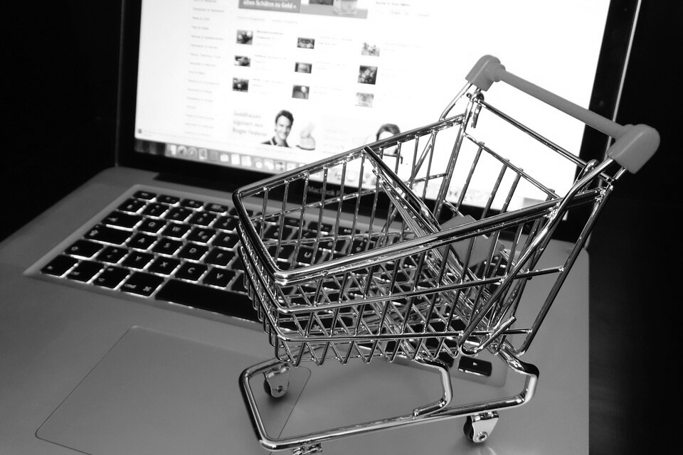 laptop with a toy shopping trolley sitting on the keys